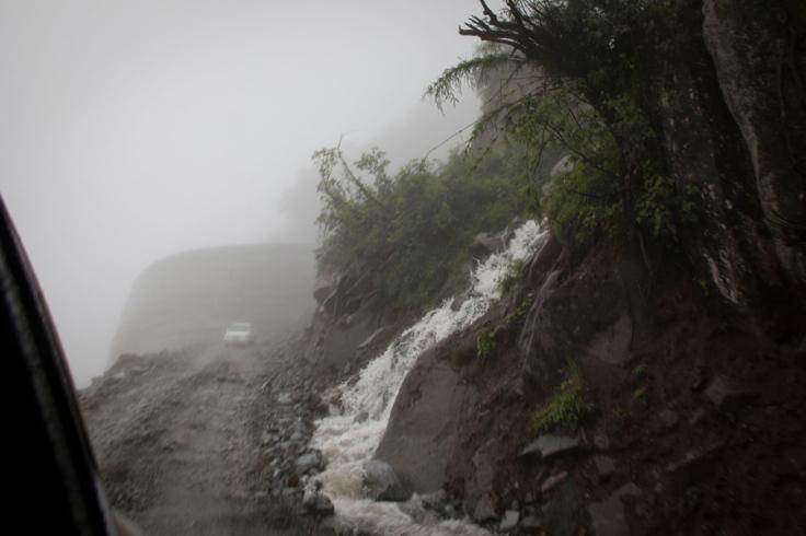 2013å¹?æœ?日,西藏墨脱扎墨路的嘎隆拉隧道附近,车辆在道路上崎岖的道路上行驶。一到雨季,道路经常被山上的流水冲毁ã€